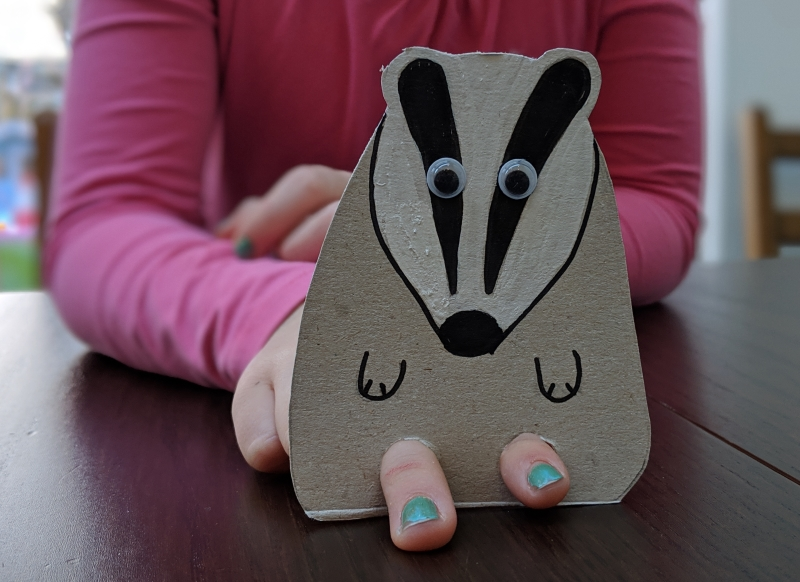 Child using a cardboard badger puppet