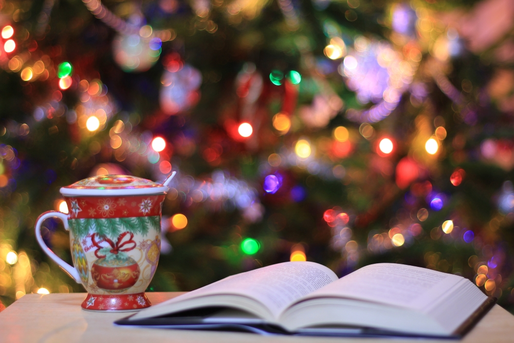 Book and christmas mug in front of a christmas tree