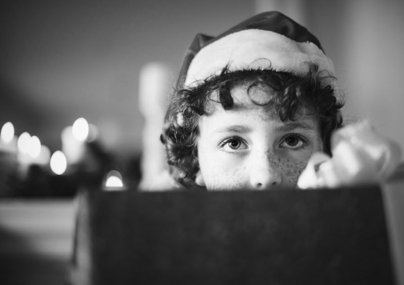 Child in a santa hat looking at the camera