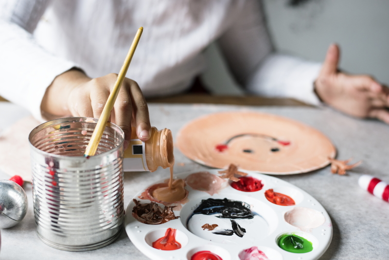 Child pouring paint into a tray for a craft activity