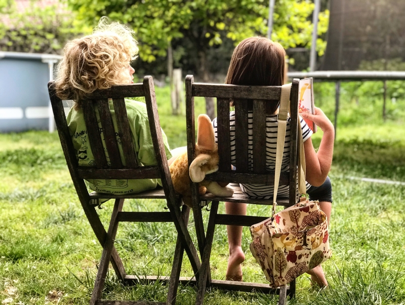 Girl and boy sat on garden chairs reading
