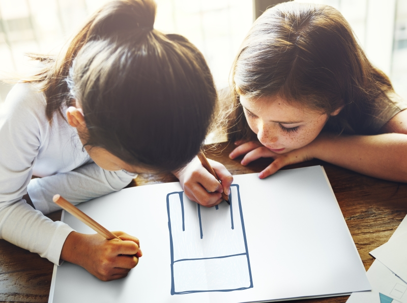 Two girls drawing a chef's hat