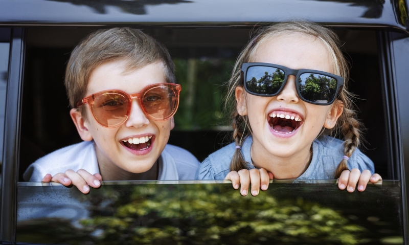 Two happy children looking out of a car with sunglasses on