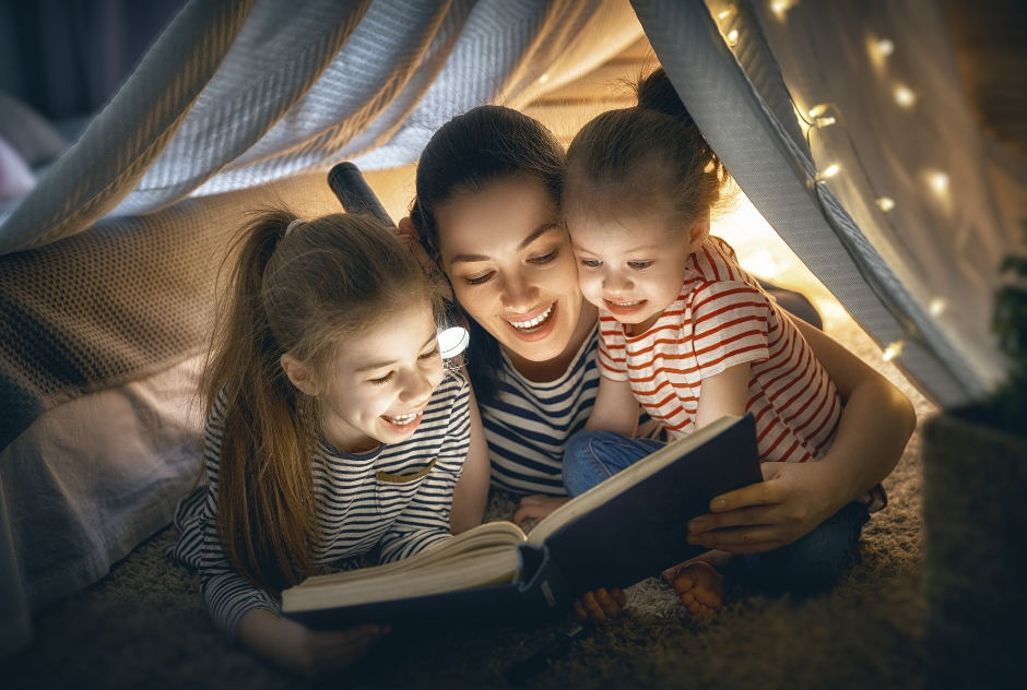 Mother reading to two children by torchlight