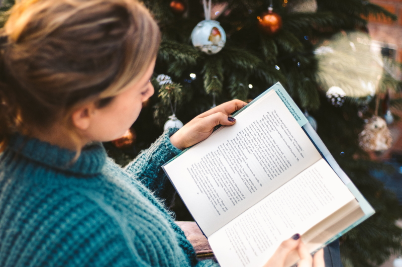 Woman reading in front of a Christmas tree