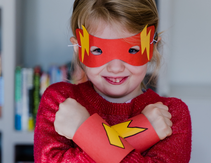Smiling child wearing superhero cuffs and mask
